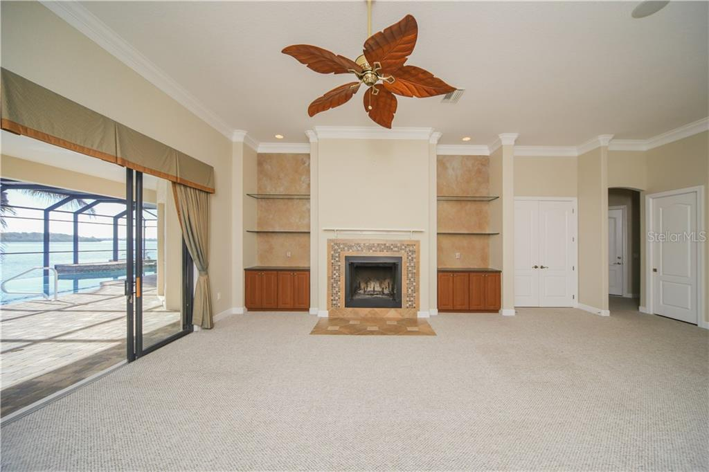 Great Room with Built-Ins on either side of Fireplace. Sliders opening to the Over-Sized Lanai & Infinity Pool - Single Family Home for sale at 550 Coral Creek Dr, Placida, FL 33946 - MLS Number is D5917129
