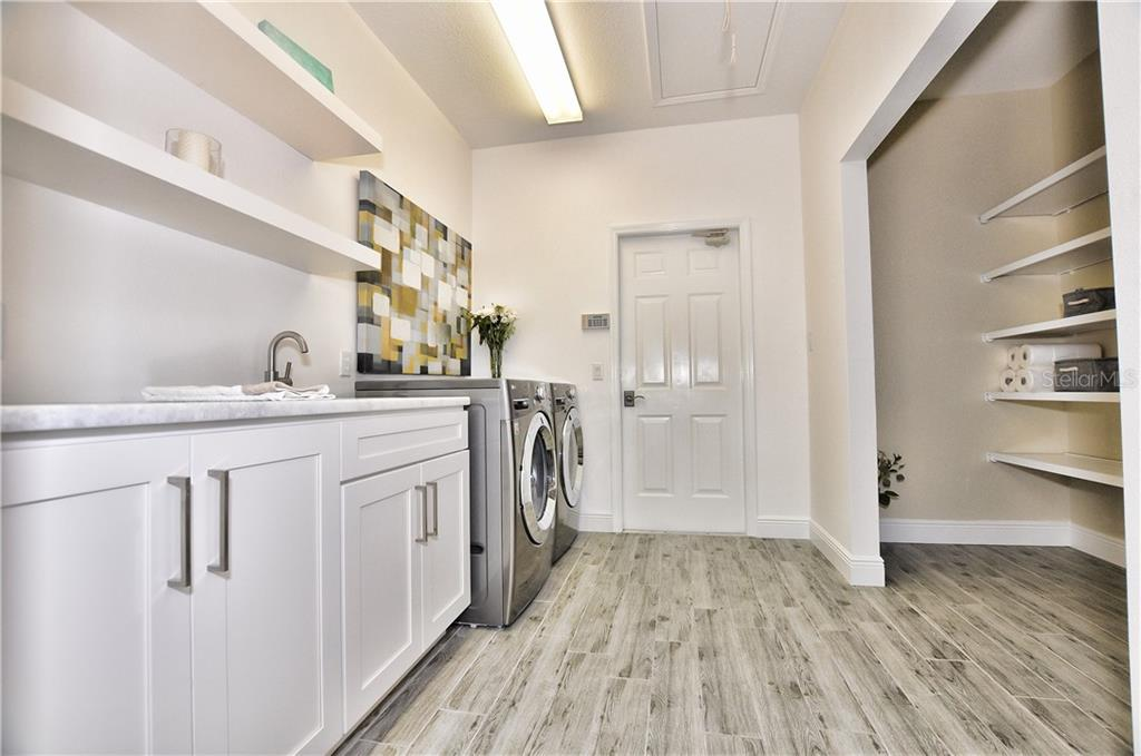 The inside laundry room has a barn door pantry with wood shelving. The laundry room features a sink and open into the 3 car garage. - Single Family Home for sale at 3121 Rivershore Ln, Port Charlotte, FL 33953 - MLS Number is D5917816