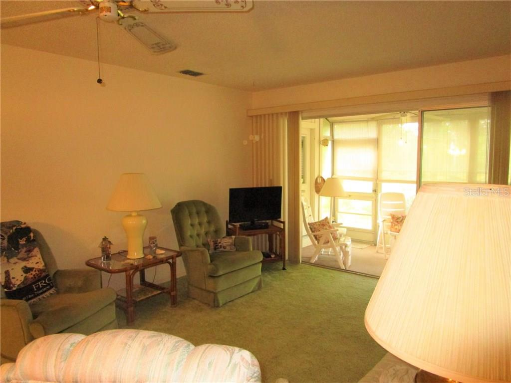 Living room has sliding glass doors leading to vinyl covered Lanai. - Condo for sale at 6796 Gasparilla Pines Blvd #14, Englewood, FL 34224 - MLS Number is D5919892