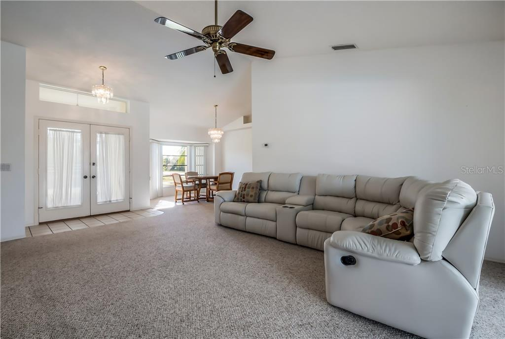 Large formal living room with view of the pool area - Single Family Home for sale at 11010 Deerwood Ave, Englewood, FL 34224 - MLS Number is D5921766