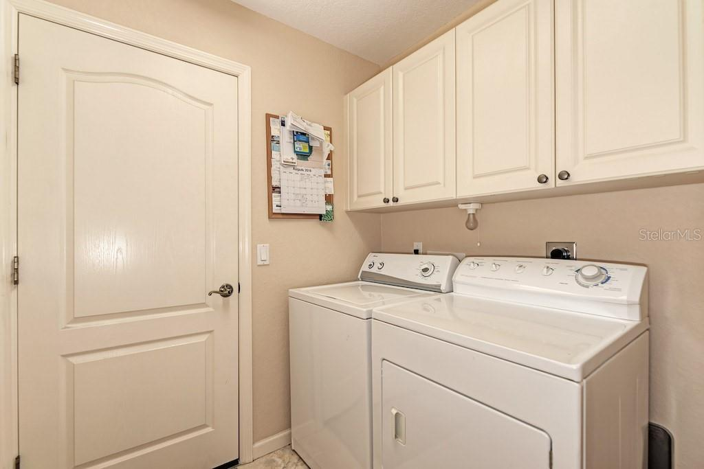 Laundry room with storage cabinets. - Single Family Home for sale at 7256 Holsum St, Englewood, FL 34224 - MLS Number is D6101787