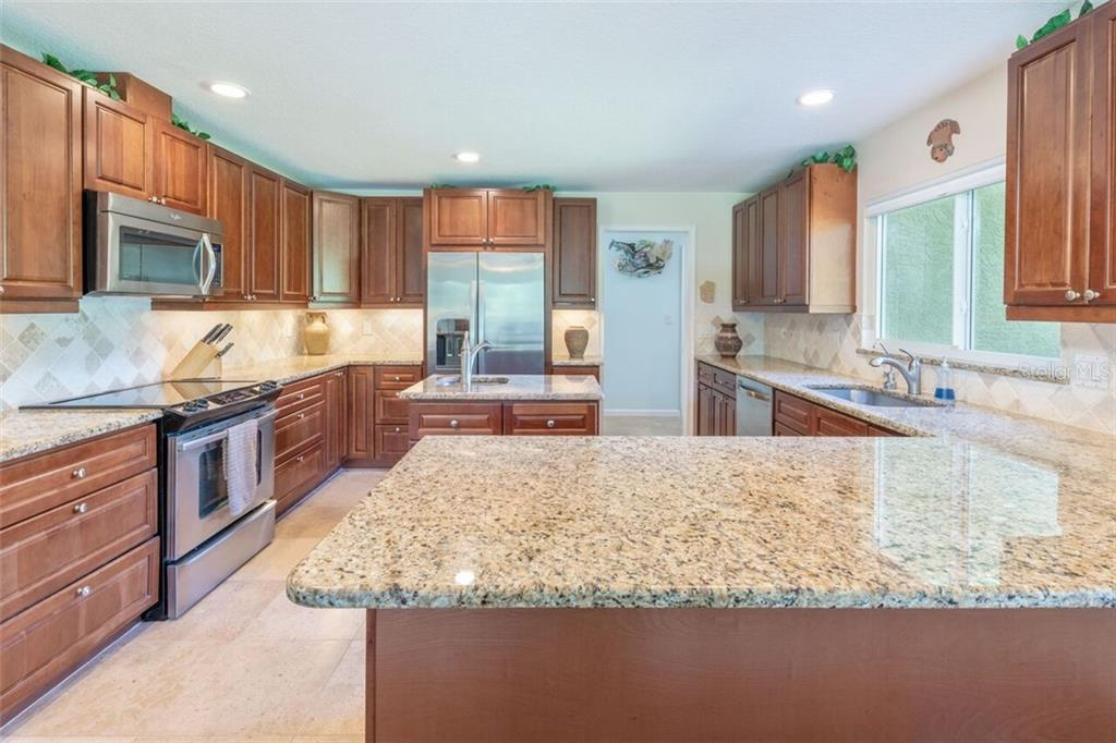 The kitchen features stainless appliances, under cabinet lighting, granite counter tops, prep island with sink, soft close drawers and door and solid wood cherry cabinetry with a Turkish travertine floor. - Single Family Home for sale at 7339 Hawkins Rd, Sarasota, FL 34241 - MLS Number is D6102762