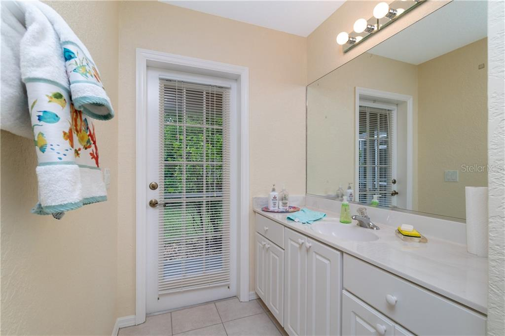 Guest bath has large vanity and access to the Lanai & pool area. - Single Family Home for sale at 30 Medalist Way, Rotonda West, FL 33947 - MLS Number is D6106239