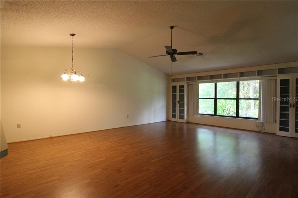 Large Living Room/Dining Room with Built-Ins on either side of windows & Breakfast Bar - Villa for sale at 420 Pendleton Dr, Venice, FL 34292 - MLS Number is D6109987