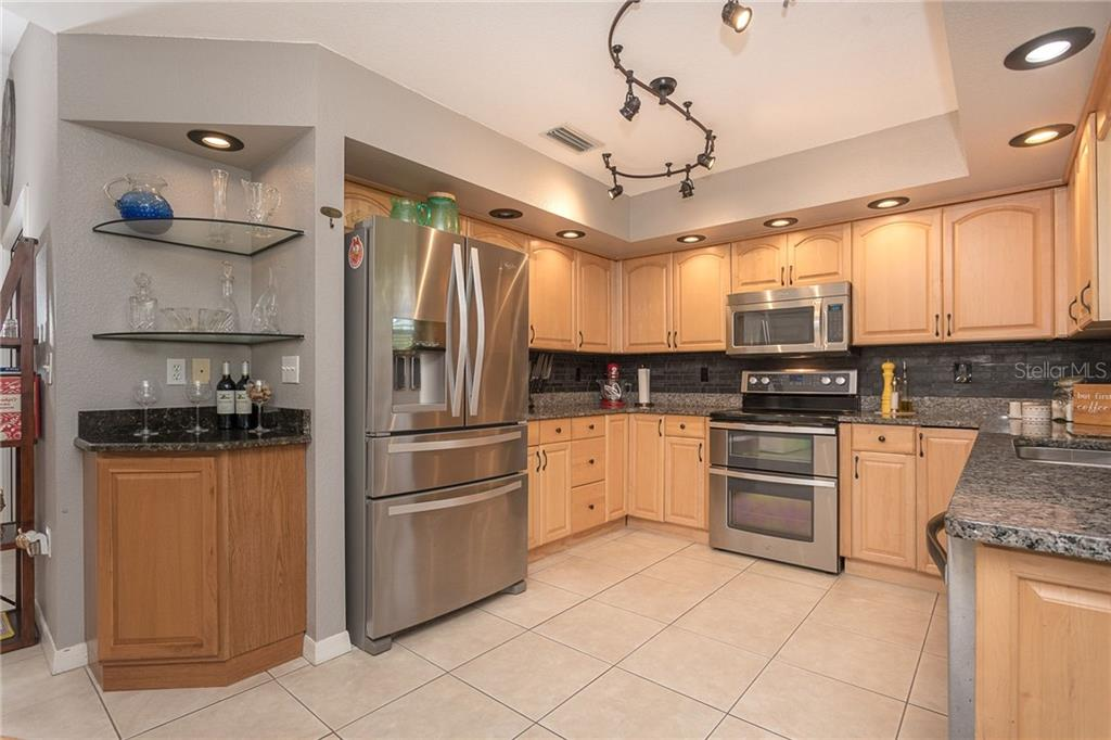 Stainless steel appliances, wood cabinets and granite counters in the open kitchen make for easy care and perfect for gathering with friends and family. - Single Family Home for sale at 185 Apollo Dr, Rotonda West, FL 33947 - MLS Number is D6113690