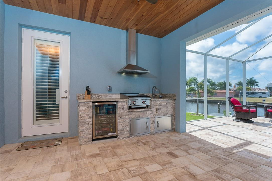 Outdoor kitchen with commercial gas grill, stainless range hood and bar refrigerator. Cypress ceilings and paver patio make this your perfect outdoor getaway just steps from the pool or dock. - Single Family Home for sale at 145 Leland St Se, Port Charlotte, FL 33952 - MLS Number is D6117438