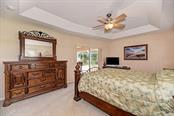 Master bedroom with tray ceiling and sliders to the lanai. - Single Family Home for sale at 7256 Holsum St, Englewood, FL 34224 - MLS Number is D6101787