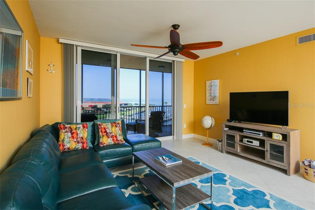 This bright and tropical great room enjoys terrific views out to Burnt Store Marina main entrance channel.  Simply slide open the impact glass sliders and enjoy balmy breezes! - Condo for sale at 3313 Sunset Key Cir #402, Punta Gorda, FL 33955 - MLS Number is C7236886