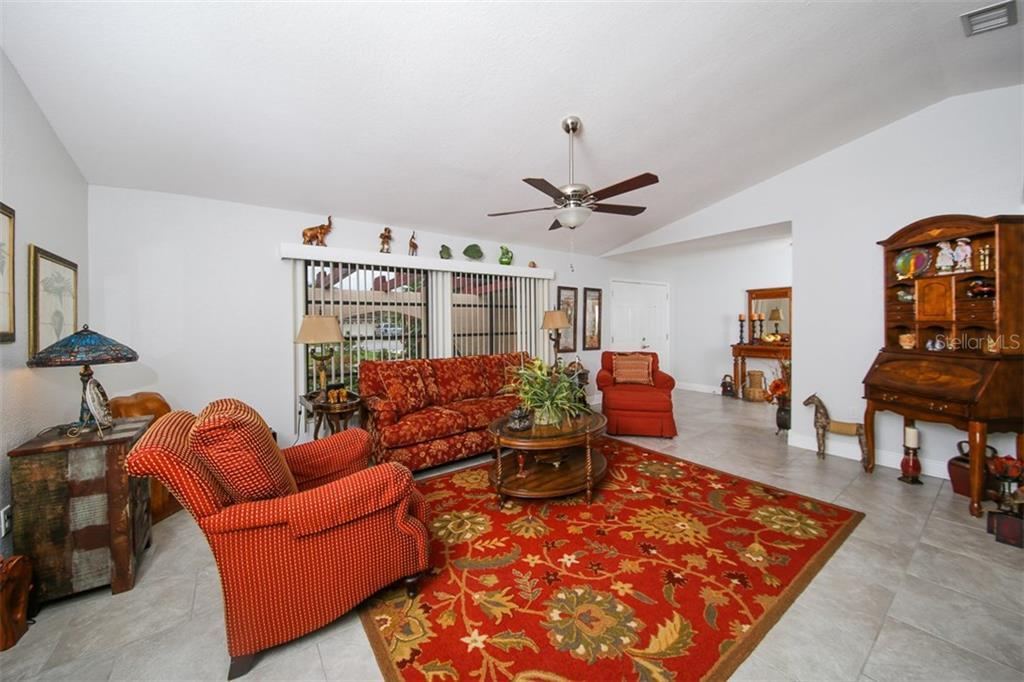 Living room and entire home is tiled throughout in lovely random pattern - redone in the last few years - Single Family Home for sale at 26178 Rampart Blvd, Punta Gorda, FL 33983 - MLS Number is C7240559