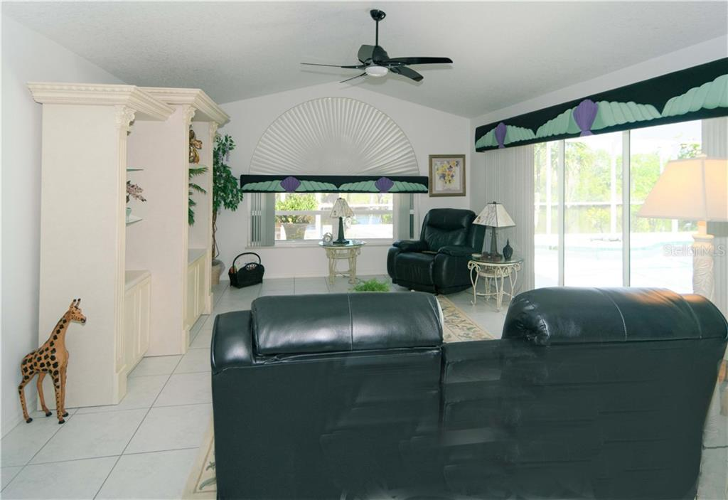 Generous sized family room (20x14) faces canal and pool area.  The custom shade and window treatments add to the beauty of this room - Single Family Home for sale at 9199 Key West St, Port Charlotte, FL 33981 - MLS Number is C7403206