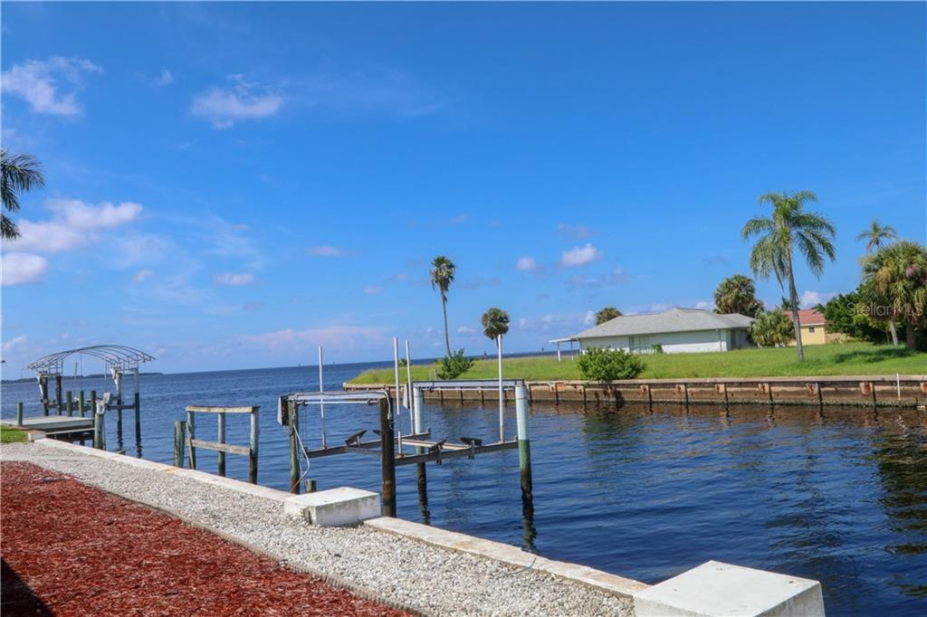 View of the canal and Charlotte Harbor from corner of property facing neighbor's boat lift.  NO BRIDGES out to the harbor which then leads to the Gulf. - Single Family Home for sale at 4449 Crews Ct, Port Charlotte, FL 33952 - MLS Number is C7405049