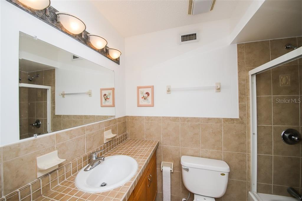 Owners ensuite bath with tiled walls & tub/shower. - Single Family Home for sale at 126 Bangsberg Rd Se, Port Charlotte, FL 33952 - MLS Number is C7409866