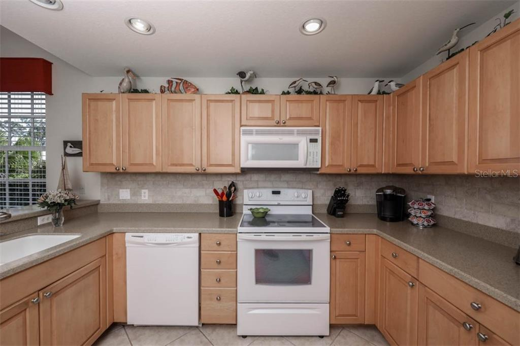 Kitchen has wood cabinets and solid surface counters - Condo for sale at 4643 Club Dr #102, Port Charlotte, FL 33953 - MLS Number is C7413207