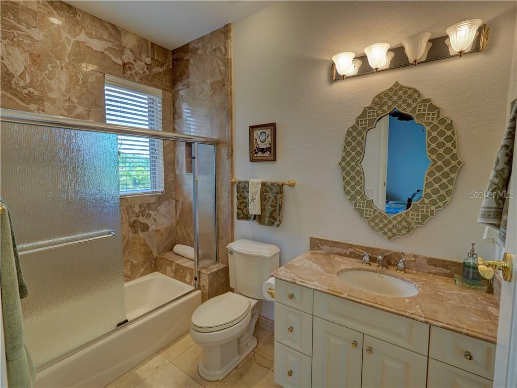 Guest room featuring garden-view front balcony includes en-suite bathroom. - Single Family Home for sale at 6150 Manasota Key Rd, Englewood, FL 34223 - MLS Number is C7415176