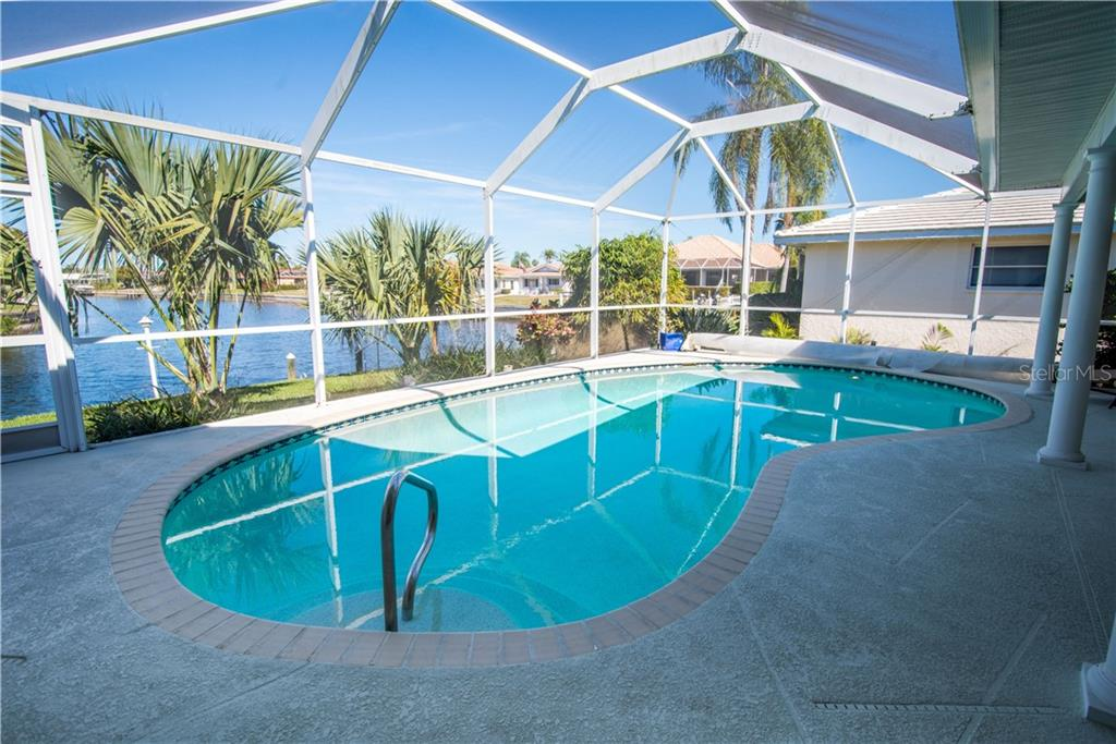 This heated pool highlights the incredible long, intersecting canal views beyond the well-manicured landscaping. - Single Family Home for sale at 1440 Appian Dr, Punta Gorda, FL 33950 - MLS Number is C7425399