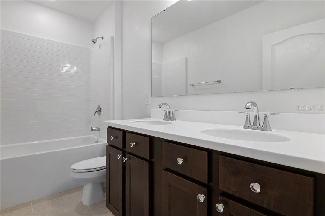 A view of the guest bathroom with dual sinks/shower-tub. - Single Family Home for sale at 2082 Apian Way, Port Charlotte, FL 33953 - MLS Number is C7441465