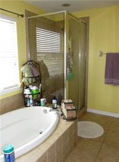 Master bath with tiled glass enclosure and soaking tub. - Single Family Home for sale at 24041 Canal St, Port Charlotte, FL 33980 - MLS Number is C7400879