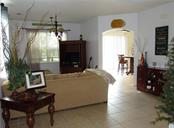 Living room with high ceilings and tiled floors on the first floor. - Single Family Home for sale at 24041 Canal St, Port Charlotte, FL 33980 - MLS Number is C7400879