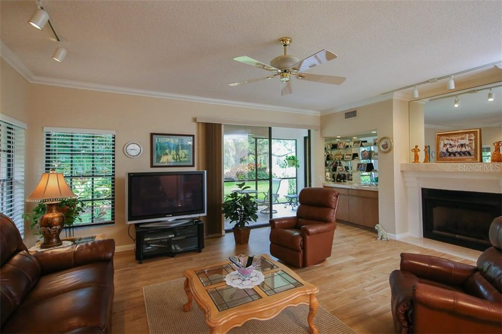 Living room with fireplace and sliders to lanai - Condo for sale at 7631 Fairway Woods Dr #601, Sarasota, FL 34238 - MLS Number is A4168292