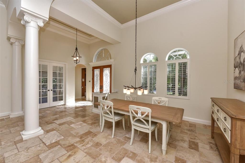 Spacious dining room. 15' ceilings and tumbled marble tile create a grand effect. - Single Family Home for sale at 3313 Founders Club Dr, Sarasota, FL 34240 - MLS Number is A4169443