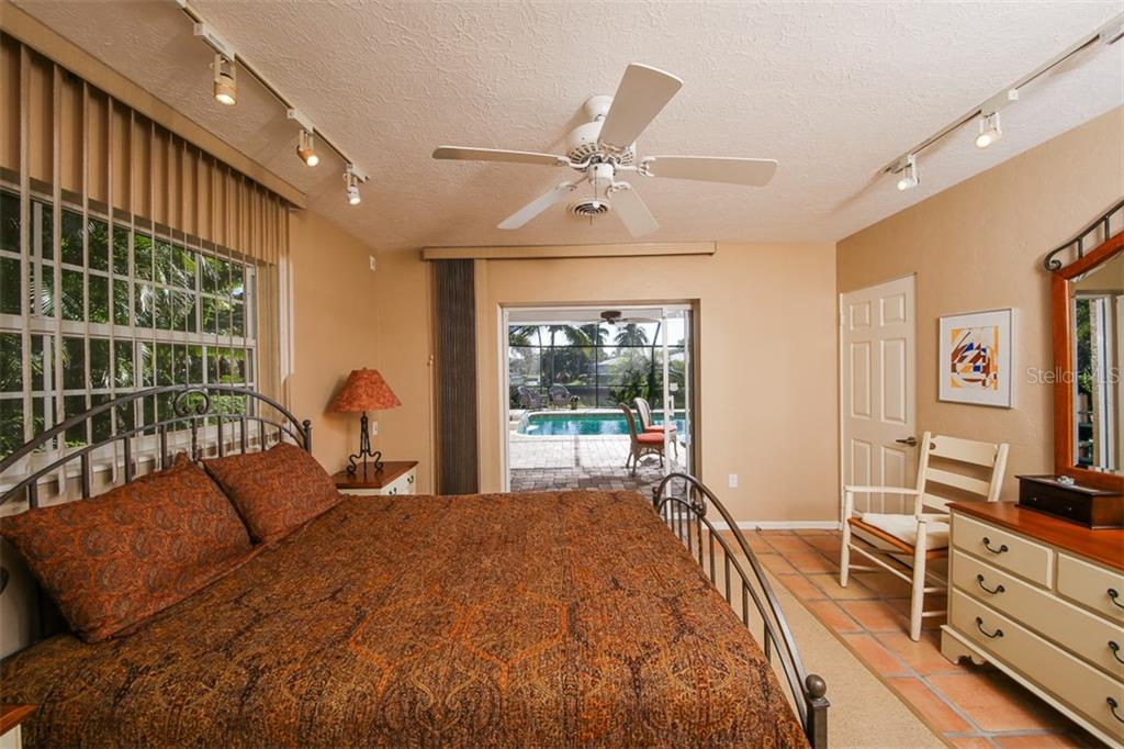 Guest ensuite bedroom with pool access through slider.  Water views! - Single Family Home for sale at 5281 Cape Leyte Way, Sarasota, FL 34242 - MLS Number is A4171478