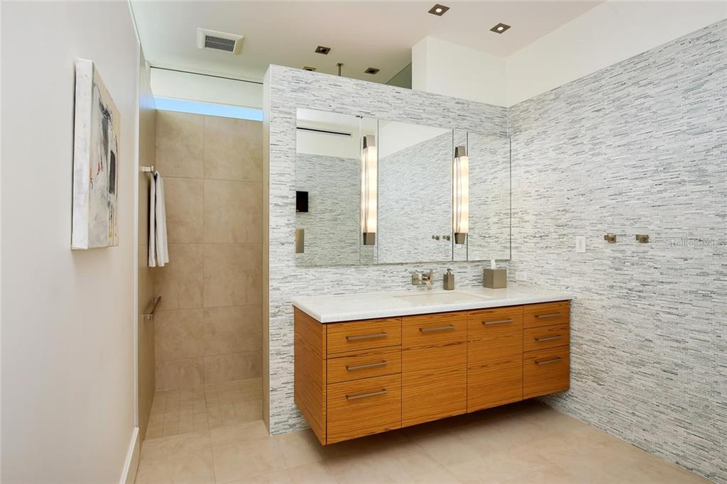 HIS master suite bathroom includes fog free mirror, walk-in shower with rain head, urinal, extra deep teak cabinetry, and Dornbracht fixtures. - Single Family Home for sale at 593 Rountree Dr, Longboat Key, FL 34228 - MLS Number is A4172941
