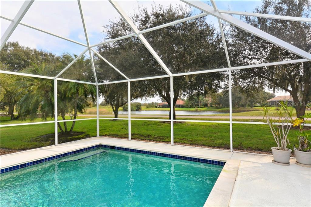 Mature grand oak trees and rolling green grass around the lake. - Single Family Home for sale at 3111 Dick Wilson Dr, Sarasota, FL 34240 - MLS Number is A4176685