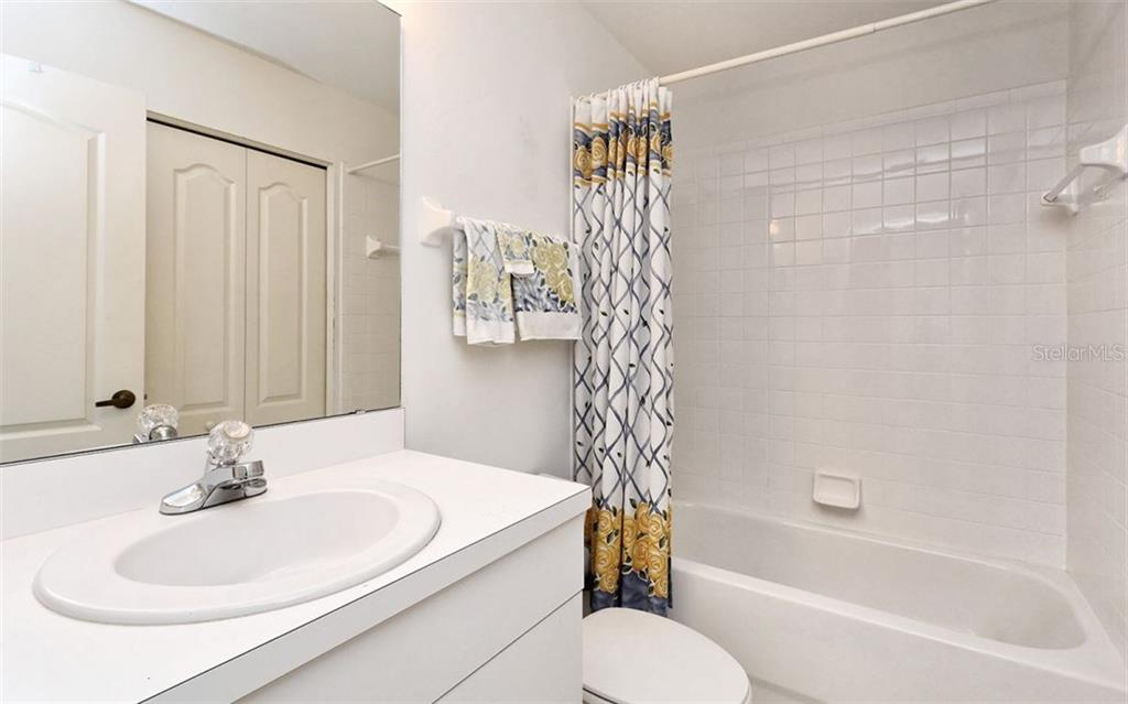 Guest bath also hosts the washer and dryer behind the bi-fold doors. - Condo for sale at 8750 Olde Hickory Ave #9305, Sarasota, FL 34238 - MLS Number is A4178271