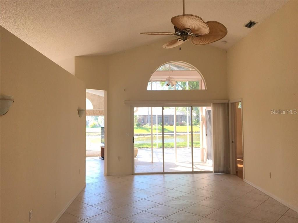 LIGHT BRIGHT LIVING ROOM--DEN IS TO THE LEFT.  LOVELY VIEW OF LAKE. - Single Family Home for sale at 1203 Harbor Town Way, Venice, FL 34292 - MLS Number is A4180060