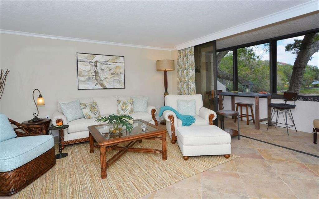 Living room with sliders to enclosed balcony - Condo for sale at 6263 Midnight Pass Rd #101, Sarasota, FL 34242 - MLS Number is A4182245
