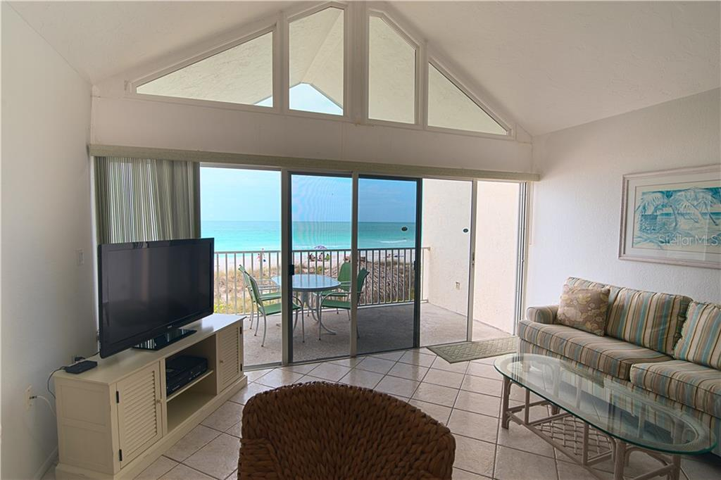 Living room and deck - Condo for sale at 100 73rd St #202a, Holmes Beach, FL 34217 - MLS Number is A4184505