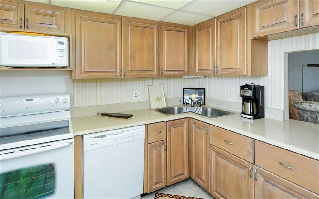 Kitchen with pass-thru to dining area - Condo for sale at 9397 Midnight Pass Rd #403, Sarasota, FL 34242 - MLS Number is A4185842