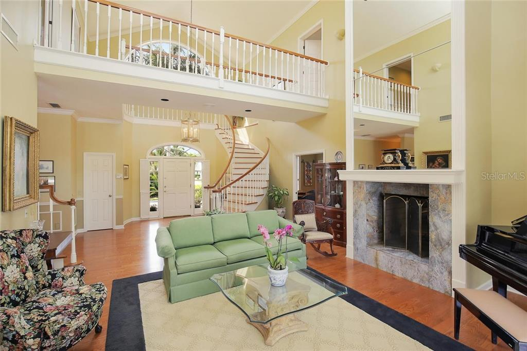 Formal living room with pass-through wood burning fireplace.  Floor to Ceiling mirrored wall and balcony view from second level.  Lots of natural light from large transom windows. - Single Family Home for sale at 3765 Beneva Oaks Blvd, Sarasota, FL 34238 - MLS Number is A4185879