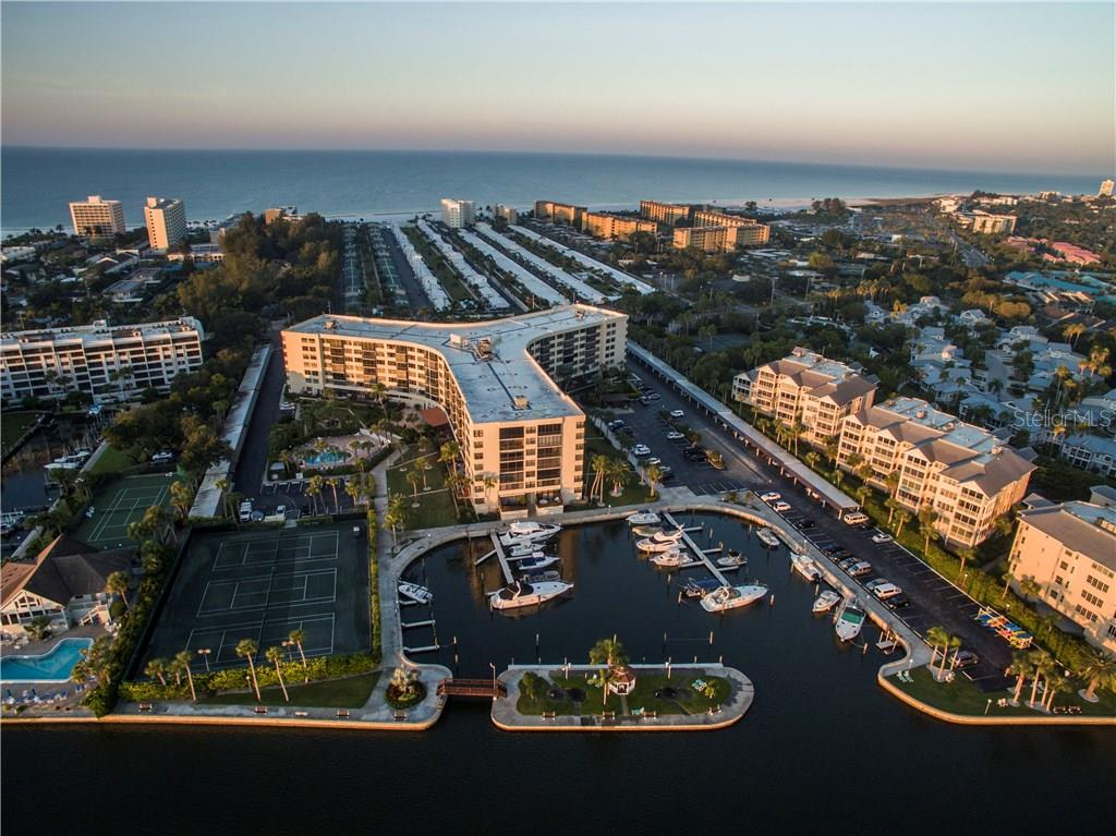 Aerial view showing marina and looking west towards Gulf of Mexico - Condo for sale at 5855 Midnight Pass Rd #628, Sarasota, FL 34242 - MLS Number is A4190416