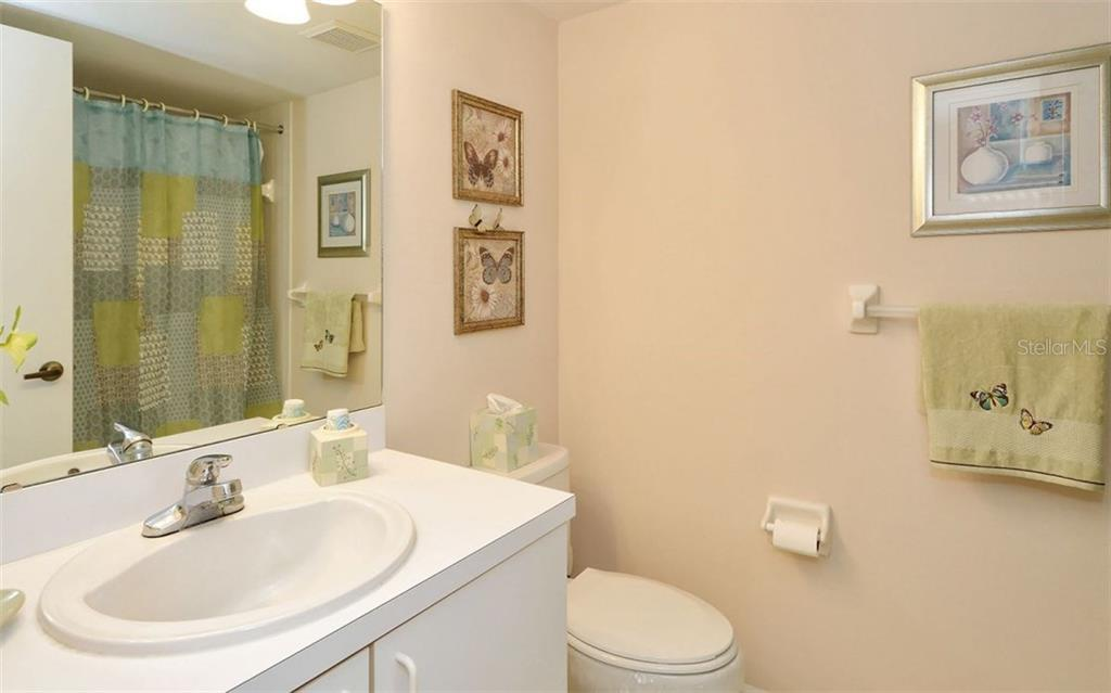 Guest bedroom with shower/tub and is adjacent to washer/dryer area. - Condo for sale at 9300 Clubside Cir #1201, Sarasota, FL 34238 - MLS Number is A4192821