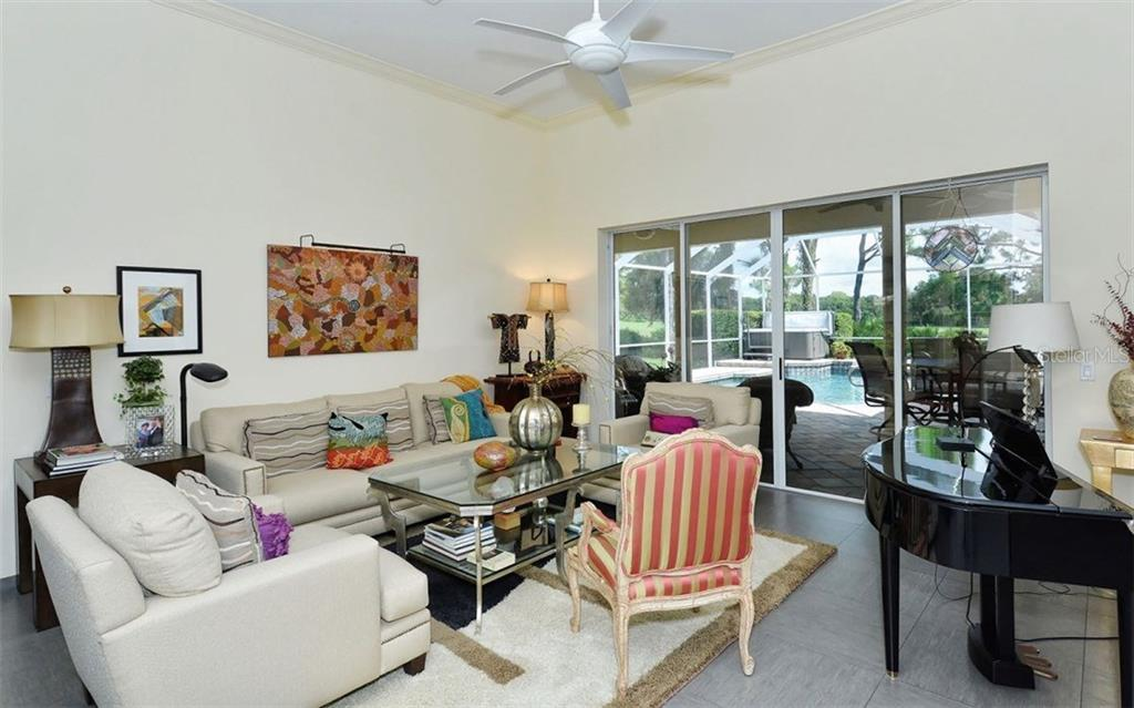 Living Room with lanai, pool and golf course views. Porcelain tile flooring and crown molding. - Single Family Home for sale at 8747 Grey Oaks Ave, Sarasota, FL 34238 - MLS Number is A4195019