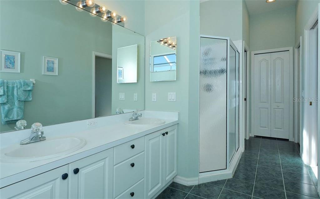 Master bath has a large separate shower.  Spacious walk-in closet is to the right of the linen closet. - Villa for sale at 9554 Forest Hills Cir, Sarasota, FL 34238 - MLS Number is A4206506