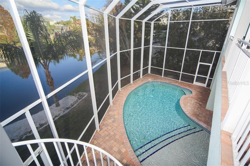 2 story pool cage with spiral stairs to main level, heated pool with brick paver deck. - Single Family Home for sale at 7047 Hawks Harbor Cir, Bradenton, FL 34207 - MLS Number is A4206626