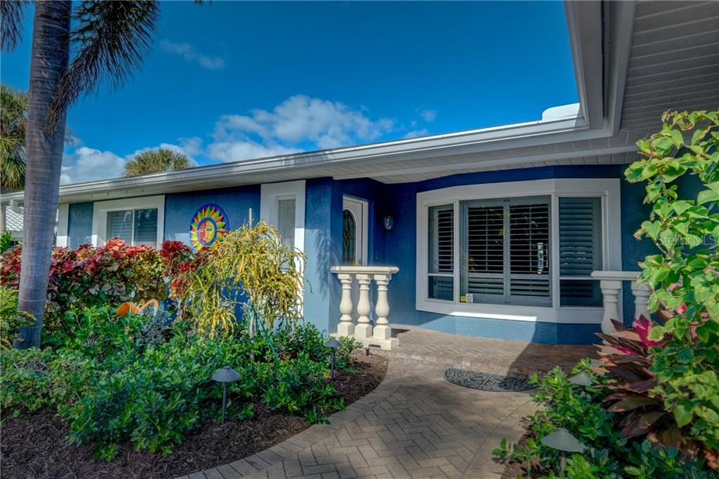 Front entry with lush plantings. - Single Family Home for sale at 5633 Cape Leyte Dr, Sarasota, FL 34242 - MLS Number is A4207008