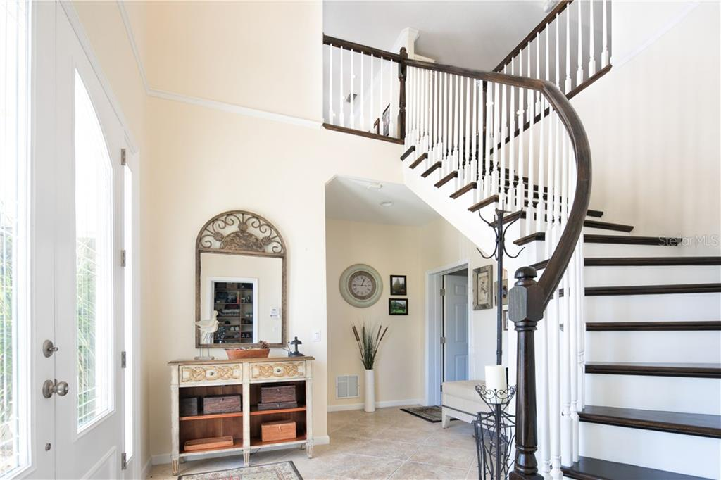 wood staircase behind the double door leads you to the living level - Single Family Home for sale at 4811 64th Dr W, Bradenton, FL 34210 - MLS Number is A4209313