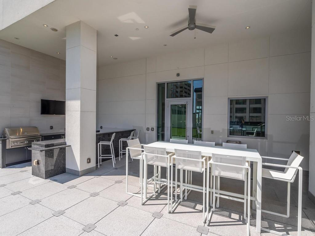 Outdoor kitchen and gathering spot located on the amenity level. - Condo for sale at 1301 Main St #1001, Sarasota, FL 34236 - MLS Number is A4402790