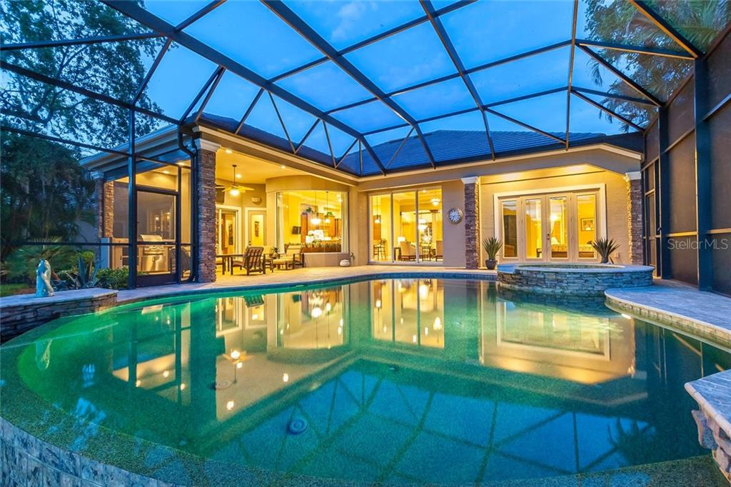 Rear of home with warm lights reflecting in the swimming pool.  Grill outside in your covered veranda and enjoy having dinner in the outdoors. - Single Family Home for sale at 12312 Newcastle Pl, Lakewood Ranch, FL 34202 - MLS Number is A4403090
