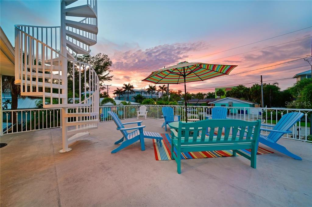 The huge 25' x 25' second floor deck is a great place to take in the sun and catch the gulf breeze.  The spiral staircase goes to a heavenly upper deck several feet above the roof where beautiful gulf views await. - Single Family Home for sale at 113 36th St, Holmes Beach, FL 34217 - MLS Number is A4407267