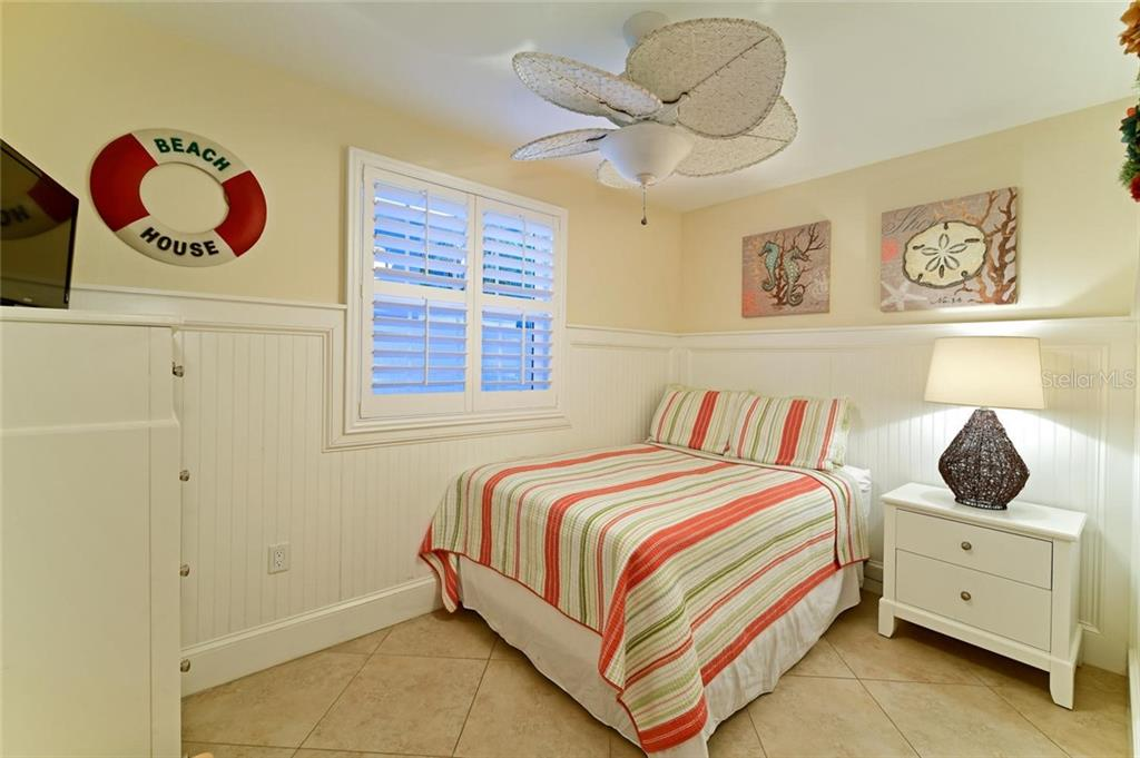 The second downstairs bedroom has a huge ceiling fan to provide a cool comfort to its occupants. - Single Family Home for sale at 113 36th St, Holmes Beach, FL 34217 - MLS Number is A4407267