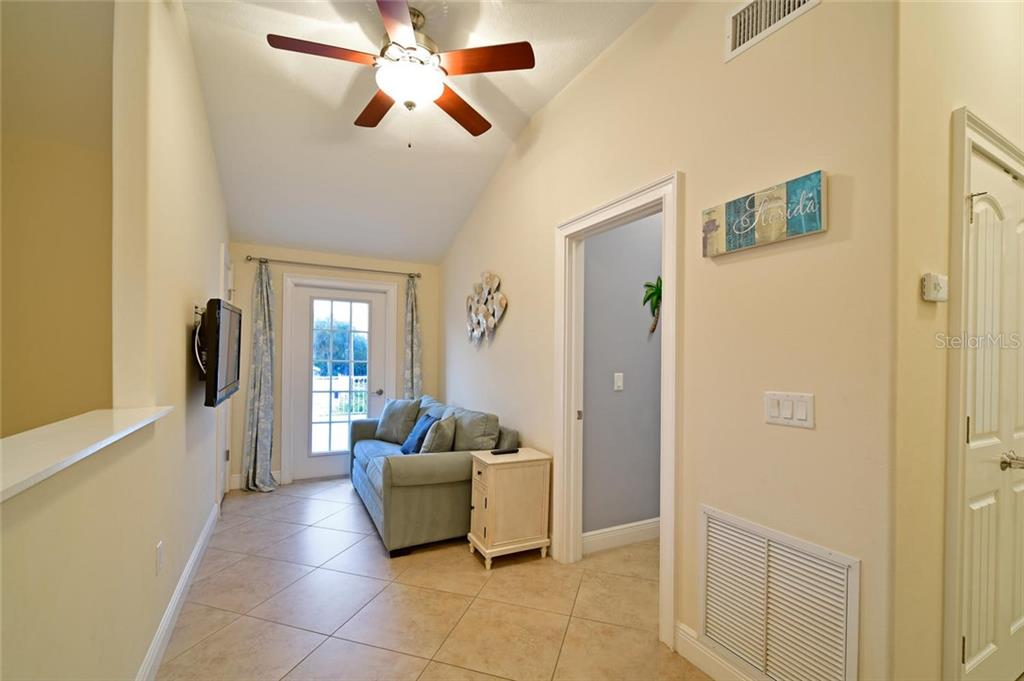 Hallway leading to the large second story deck offers a chance to check out how the televised game is going, or just a quiet place to read. - Single Family Home for sale at 113 36th St, Holmes Beach, FL 34217 - MLS Number is A4407267
