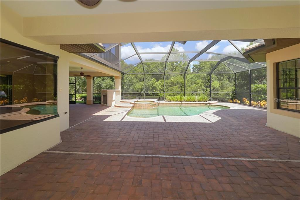 The lower level pavered lanai has multiple seating and entertainment spaces, including an area with fireplace and another with an outdoor kitchen. - Single Family Home for sale at 13219 Palmers Creek Ter, Lakewood Ranch, FL 34202 - MLS Number is A4407857