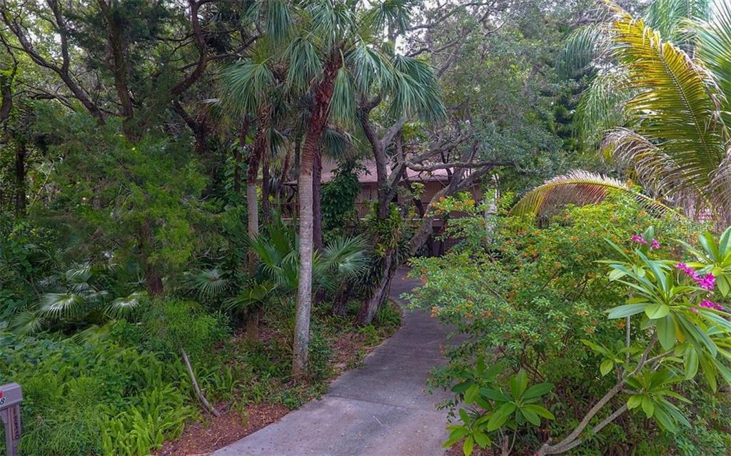 Tropical Landscaping Surrounds Driveway - Single Family Home for sale at 1238 Sea Plume Way, Sarasota, FL 34242 - MLS Number is A4408272