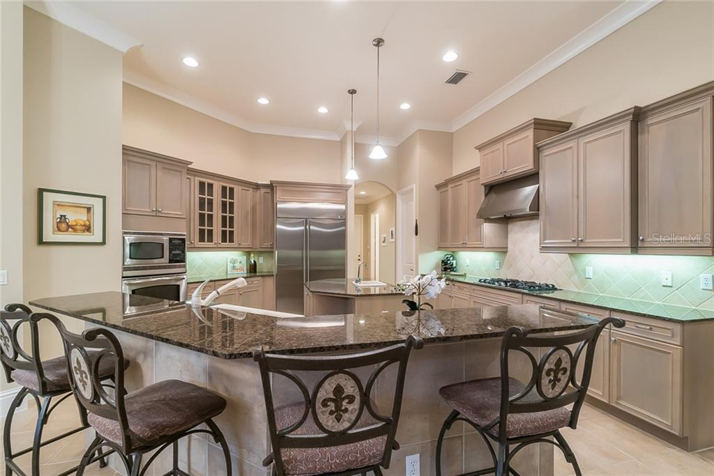 Gourmet Kitchen features an island with vegetable sink, 5 burner gas stovetop, stainless steel appliances, and granite counters. - Single Family Home for sale at 13223 Palmers Creek Ter, Lakewood Ranch, FL 34202 - MLS Number is A4408290