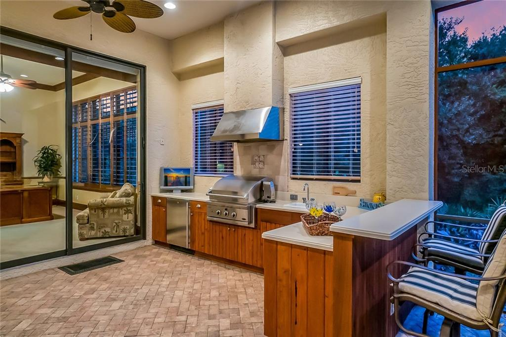 Outdoor Kitchen includes a refrigerator, grill with rotisserie, sink, and  plenty of cabinets & counter space with bar seating. - Single Family Home for sale at 13223 Palmers Creek Ter, Lakewood Ranch, FL 34202 - MLS Number is A4408290