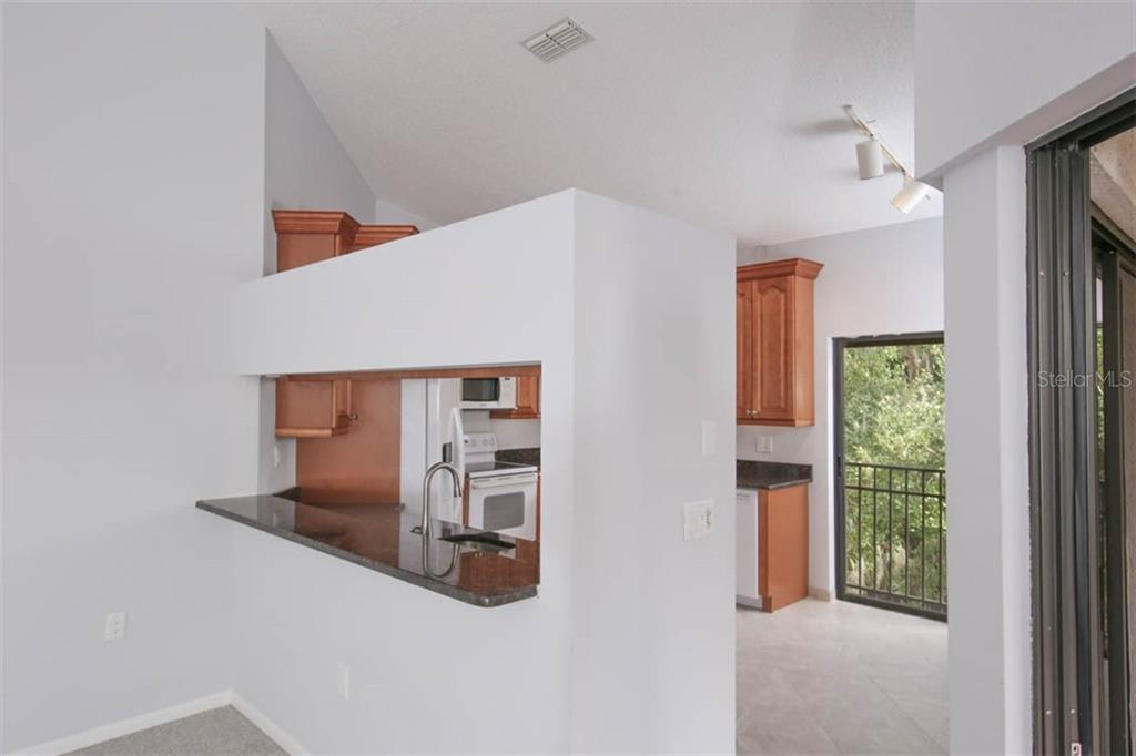 Prep center, serving bar, cafe dining w/treetop view and a peek of Lake Starling out back. - Condo for sale at 1716 Starling Dr #204, Sarasota, FL 34231 - MLS Number is A4412237